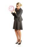 Donna di affari sorpresa che tiene un grande orologio Immagine Stock