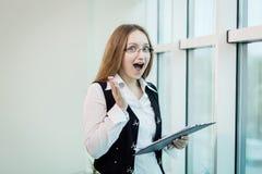 Donna di affari sorpresa con il documento Screa stupito della donna di affari Fotografie Stock Libere da Diritti