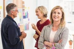 Donna di affari sorridente avanti con il suo gruppo dietro Immagini Stock