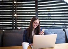 Donna di affari sorridente che chiacchiera tramite telefono cellulare, sedentesi con il computer portatile nell'interno del risto Immagine Stock Libera da Diritti