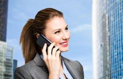 Donna di affari sorridente che comunica sul telefono fotografia stock libera da diritti