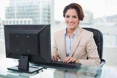 Donna di affari sorridente che esamina macchina fotografica Immagini Stock