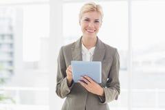 Donna di affari sorridente che esamina macchina fotografica e per mezzo della sua compressa Fotografia Stock