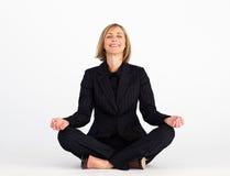 Donna di affari sorridente che fa le esercitazioni di yoga Immagini Stock