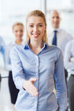 Donna di affari sorridente che fa stretta di mano in ufficio Fotografie Stock Libere da Diritti