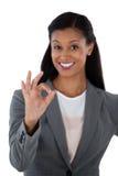 Donna di affari sorridente che gesturing il segno giusto della mano Immagini Stock