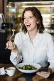 Donna di affari sorridente che ha lucnch al caffè all'interno immagine stock libera da diritti