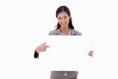 Donna di affari sorridente che indica alla scheda in bianco del segno immagine stock libera da diritti