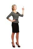 Donna di affari sorridente che indica su, isolato sopra fotografia stock