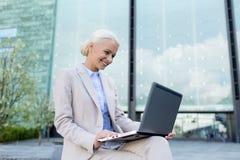 Donna di affari sorridente che lavora con il computer portatile all'aperto Fotografia Stock