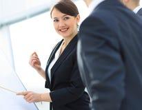 Donna di affari sorridente che mostra informazioni del collega sul flipchart Immagini Stock