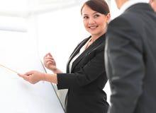 Donna di affari sorridente che mostra informazioni del collega sul flipchart Fotografie Stock Libere da Diritti
