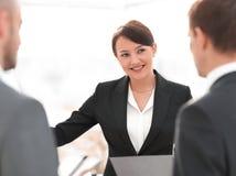 Donna di affari sorridente che mostra informazioni del collega sul flipchart Fotografia Stock