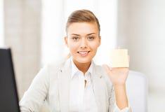 Donna di affari sorridente che mostra nota appiccicosa Fotografia Stock Libera da Diritti