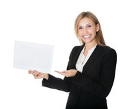 Donna di affari sorridente che mostra una scheda bianca in bianco fotografia stock