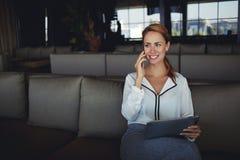 Donna di affari sorridente che parla sul telefono cellulare con il cliente mentre sedendosi con la compressa digitale in ristoran Immagini Stock Libere da Diritti