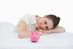 Donna di affari sorridente che pende sul suo scrittorio con un porcellino salvadanaio Fotografia Stock