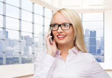 Donna di affari sorridente che rivolge allo smartphone Fotografie Stock Libere da Diritti