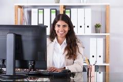 Donna di affari sorridente che scrive sulla tastiera fotografia stock libera da diritti