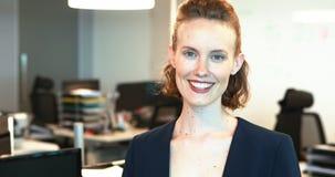 Donna di affari sorridente che si leva in piedi nell'ufficio archivi video