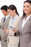 Donna di affari sorridente con il cellulare accanto ai colleghi Fotografia Stock