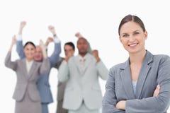 Donna di affari sorridente con il gruppo incoraggiante dietro lei Immagini Stock