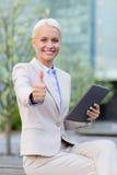 Donna di affari sorridente con il pc della compressa all'aperto Immagini Stock