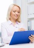 Donna di affari sorridente con la lavagna per appunti in ufficio Fotografie Stock Libere da Diritti