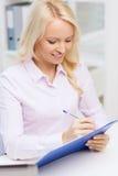 Donna di affari sorridente con la lavagna per appunti in ufficio Immagini Stock Libere da Diritti
