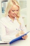 Donna di affari sorridente con la lavagna per appunti in ufficio Immagine Stock