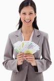 Donna di affari sorridente con le banconote in sue mani Fotografia Stock