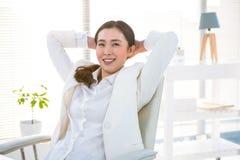 Donna di affari sorridente con le mani dietro la testa Fotografie Stock