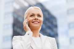 Donna di affari sorridente con lo smartphone all'aperto Fotografie Stock