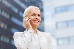 Donna di affari sorridente con lo smartphone all'aperto Fotografie Stock Libere da Diritti