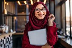 Donna di affari sorridente nel hijab alla caffetteria fotografia stock