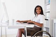 Donna di affari sorridente in sedia a rotelle che funziona al suo scrittorio fotografia stock libera da diritti