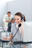 Donna di affari sorridente sul telefono al suo scrittorio Fotografia Stock Libera da Diritti