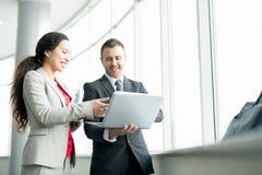 Donna di affari sorridente Talking al collega dalla finestra immagini stock libere da diritti