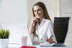 Donna di affari sorridente in ufficio fotografia stock libera da diritti