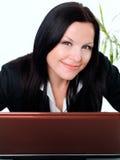 Donna di affari sorridente in ufficio con il computer portatile immagini stock