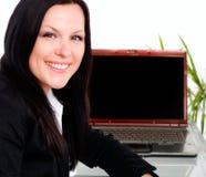 Donna di affari sorridente in ufficio con il computer portatile fotografia stock