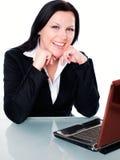 Donna di affari sorridente in ufficio con il computer portatile fotografie stock