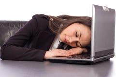 Donna di affari sovraccarica che dorme sul suo computer portatile che è esaurito Immagine Stock