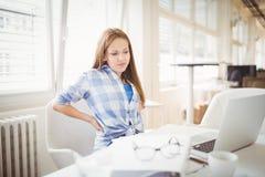 Donna di affari stanca che esamina computer portatile sullo scrittorio in ufficio fotografia stock libera da diritti