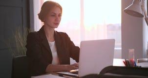 Donna di affari stanca che lavora al computer portatile all'ufficio archivi video
