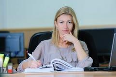 Donna di affari stanca di pensiero che tiene una penna Fotografia Stock