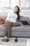 Donna di affari stancare che si siede sul sofà Immagini Stock