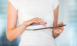 Donna di affari/studente di college graziosi e giovani che per mezzo del suo computer della compressa Fotografia Stock