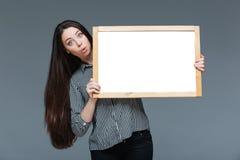 Donna di affari stupita che tiene bordo in bianco Fotografia Stock