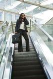 Donna di affari su una scala mobile Fotografia Stock
